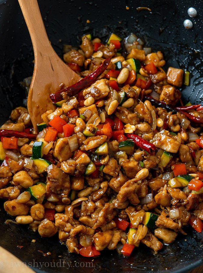Kung Pao Chicken in wok with vegetables and spoon