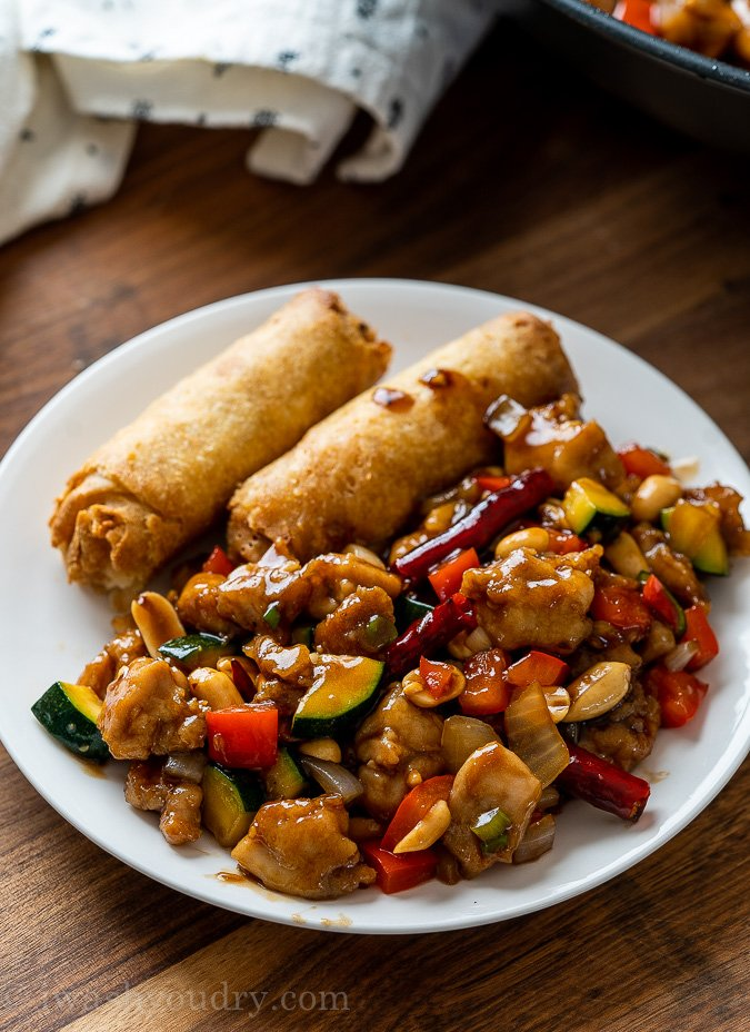 chinese kung pao chicken with egg rolls on plate
