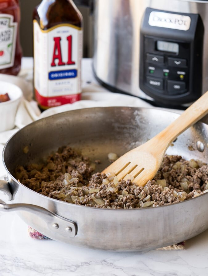 Start by browning some beef in a skillet with onions to make this Crock Pot Baked Beans recipe.