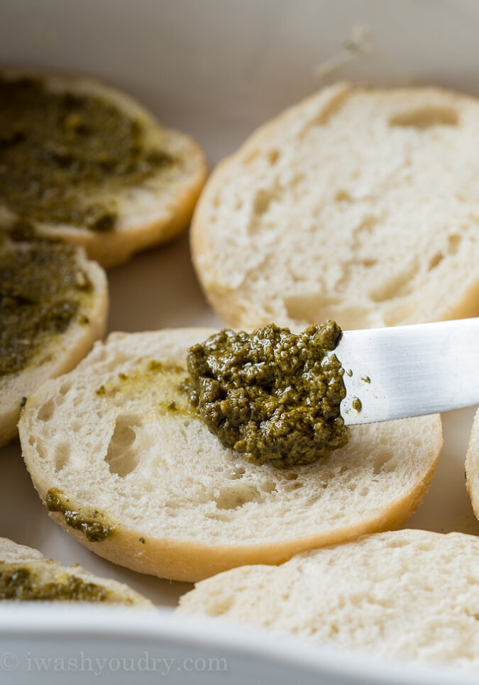 Spread a little bit of basil pesto over the bottom half of each savory garlic knot and place in a baking sheet.