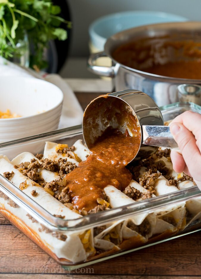 Once you've filled your casserole dish with the easy ground beef enchiladas, spread more enchilada sauce over the top and add some cheese!