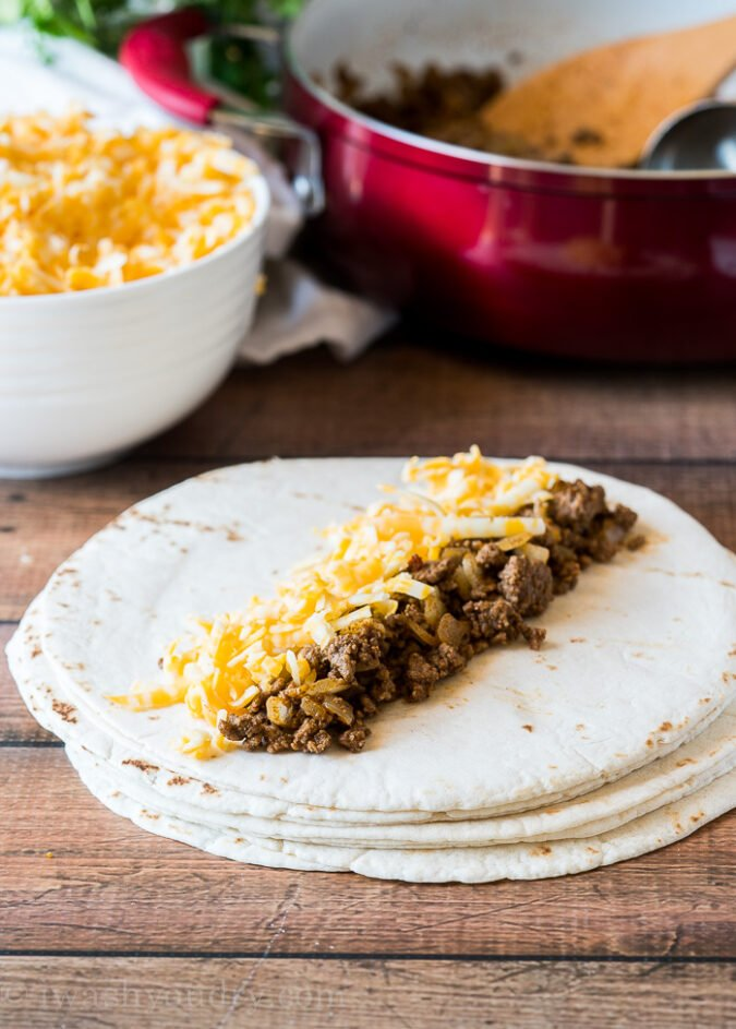 To start making these ground beef enchiladas, start by adding about 1/3 cup of seasoned ground beef and cheese to the center of a small tortilla, then roll up and place in your 9x13 inch casserole dish.
