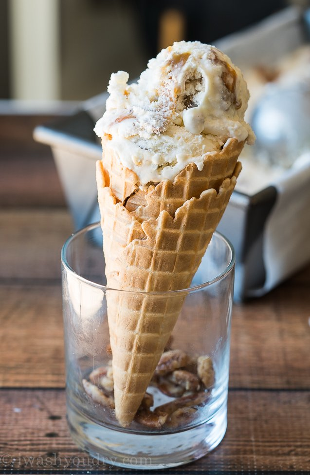 Cool off with this super smooth and creamy Homemade Ice Cream Recipe that's filled with ribbons of caramel and chunks of candied pecans!