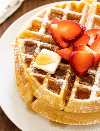 Crispy waffles on white plate with syrup and strawberries.