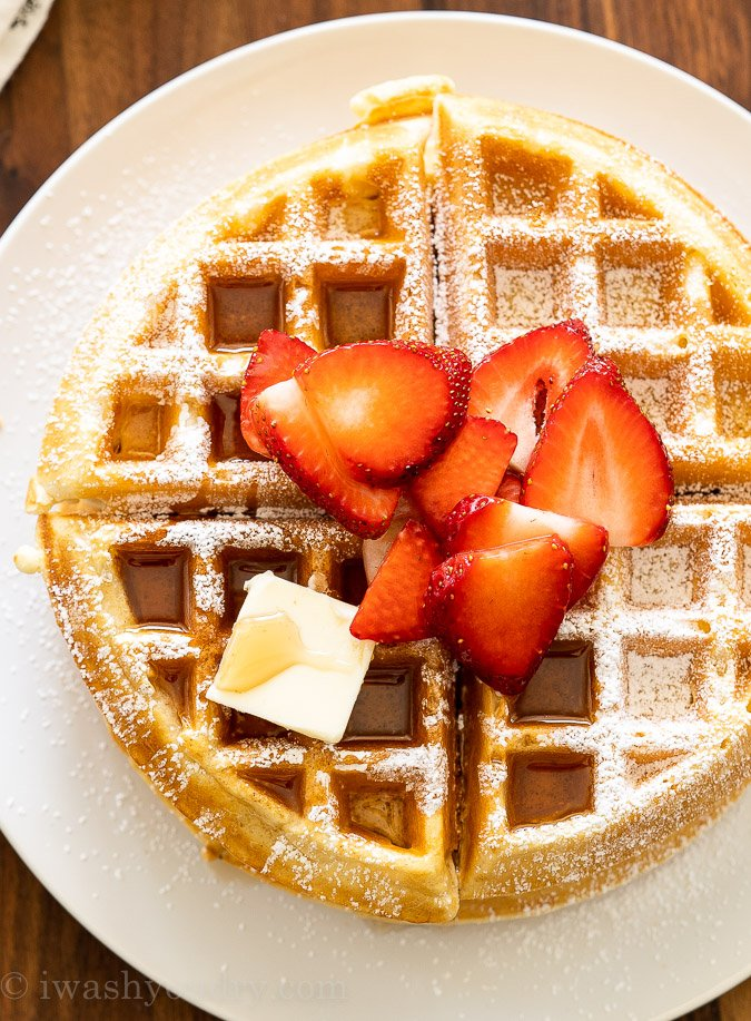 Large waffle on plate with butter and syrup