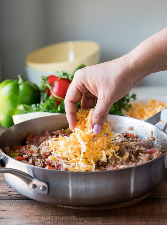 Top the cooked ground beef and rice with some cheese and add the lid back on until the cheese is melted.