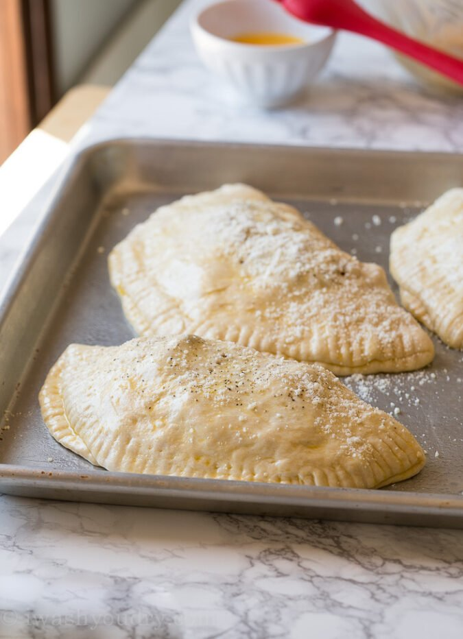 Brush the tops of each calzone with a simple egg wash, sprinkle with black pepper and grated parmesan cheese.