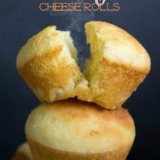 A close up of two Airy Cheese Rolls with one roll split in half
