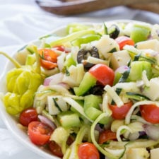 A close up of a bowl of salad, with zucchini noodles, tomatoes, olives, and other veggies