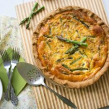 A Asparagus and Goat Cheese Quiche with a spoon next to it