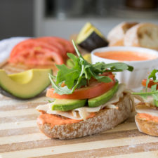 A close up of an open sandwich on a cutting board with meant, avocado, tomatoes and lettuce