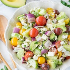 A bowl of salad, with cucumbers, avocado and tomatoes