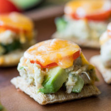 A close up of food on a table, with Avocado, Tuna, tomatoes and cheese on a cracker
