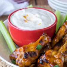 A close up of plate of food on a plate, with chicken wings, celery sticks and a small bowl of dipping sauce