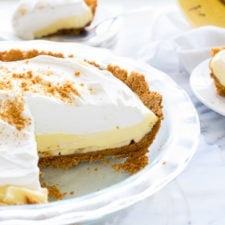 A piece of banana cream pie in a glass pie dish with a slice taken out