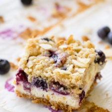 A close up of a piece of cheesecake on a plate topped with blueberries and crumble topping