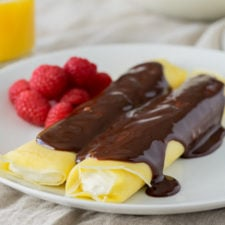 A 2 crepes on a plate topped with chocolate sauce and a side of raspberries