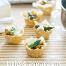 A close up of tarts on a table, filled with brie and asparagus