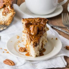 A slice of cheesecake on a plate topped with sauce and pecans.