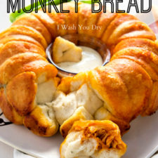 A close up of Buffalo Chicken Monkey Bread in a bundt cake shape with a small cup of dipping sauce in the center