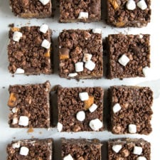 Food on a table, with squares of chocolate Rice Krispie treats