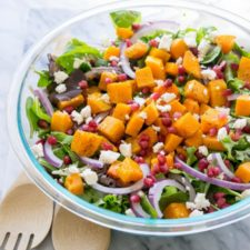 A clear glass bowl of salad on a table, with butternut squash, onions, lettuce and other veggies