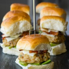 A close up of small sandwiches made from dinner rolls, with chicken, lettuce, cheese and veggies