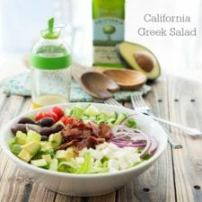 A bowl of California Greek Salad on a wooden surface