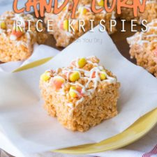 A square of a rice crispy treat on a plate, topped with candy corn and melted white chocolate