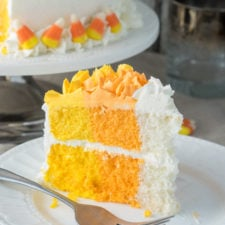 A slice of cake with yellow, orange and white layers