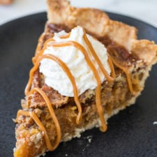 A slice of pecan pie on a plate topped with whipped cream and caramel sauce
