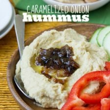 A close up of caramelized onion hummus on a veggie plate