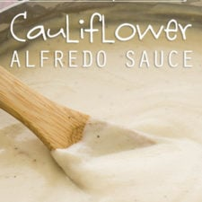 A close up of a white sauce being stirred with a wooden spoon