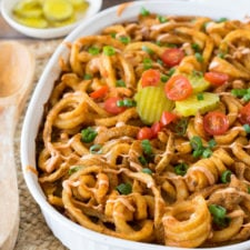 A casserole dish of pasta with hamburger, pickles, tomatoes