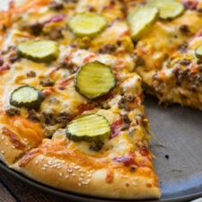 A pizza sitting on top of a pan, topped with cheese, veggies, meat and pickle slices
