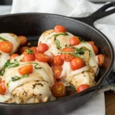 A skillet filled with baked chicken breasts topped  with cheese and tomatoes