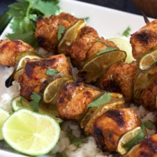 A plate with chicken chunks and lime slices on a skewers