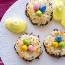 A close up of coconut dessert on a plate, topped with candied eggs and peeps on the side