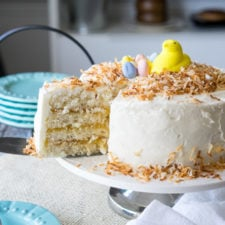 A white layer cake with white icing and a slice removed from it