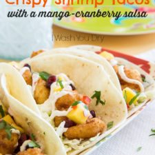 A close up of a plate of food, with soft shelled tacos with shrimp, white sauce, mango and veggies