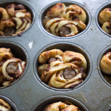 A close up of a muffin tin with Sausage Filled Cinnamon Roll Monkey Bread