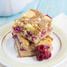 Two bars of Gooey Raspberry Coffee Cake stacked on top of each other on a plate