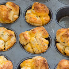 A close up of a muffin tin of Cheesy Monkey Bread Rolls