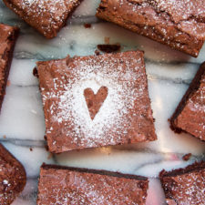 A close up of red velvet brownie squares with a powdered sugar heart on top