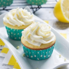 Two Lemon Burst Cupcakes in turquoise wrappers on a white plate