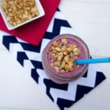 A look down on a smoothie in a glass cup with granola on top and a blue straw