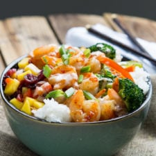 A bowl of Sweet Fire Shrimp on rice with veggies displayed on a wooden surface