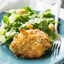 A plate of food with a breaded piece of chicken and a side of green salad