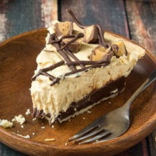 A slice of Chocolate Bottomed Peanut Butter Pie with a bite taken from it displayed on a plate