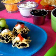 Mini Taco Bites on a plate infant of small bowls of toppings